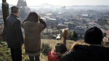 Residents look at their devastated area from a hilltop in Kesennuma, Miyagi Prefecture, northern Japan, Monday, March 14, 2011, three days after a massive earthquake and the ensuing tsunami hit Japan's east coast. (AP / Kyodo News)