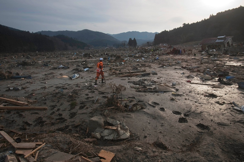 A Japanese rescue team member walks through the completely leveled village of Saito in northeastern Japan Monday, March 14, 2011. Rescue workers used chain saws and hand picks Monday to dig out bodies in Japan's devastated coastal towns, as Asia's richest nation faced a mounting humanitarian, nuclear and economic crisis in the aftermath of a massive earthquake and tsunami that likely killed thousands. (AP / David Guttenfelder)