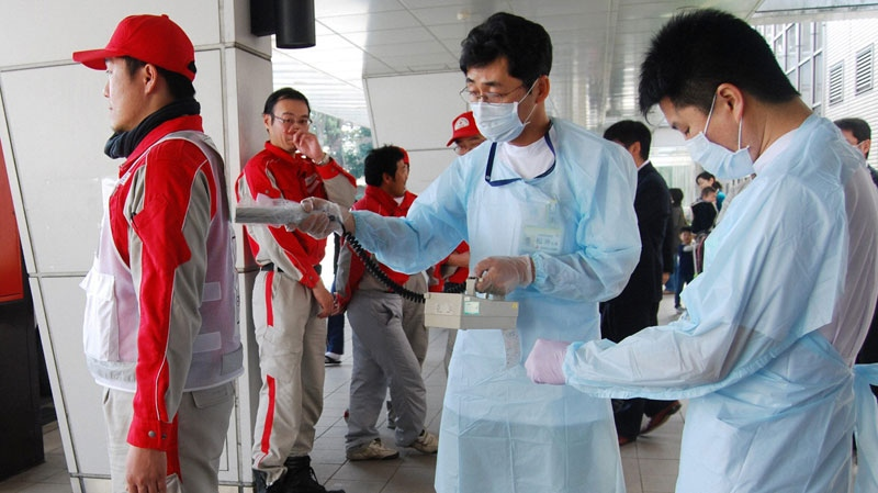 A Red Cross rescue worker, in red, is scanned for signs of radiation upon returning from Fukushima to his hospital in Nagahama, Shiga Prefecture, Monday, March 14, 2011. (AP / Kyodo News)