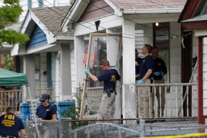 Members of the FBI evidence response team carry out the front screen door from a house where three women were held in Cleveland on Tuesday, May 7, 2013. (AP / Tony Dejak)