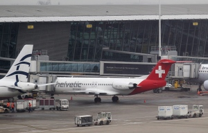 Baggage carts make their way past a Helvetic Airways aircraft from which about $50 million worth of diamonds were stolen on the tarmac of Brussels international airport Tuesday, Feb. 19, 2013. (AP / Yves Logghe)
