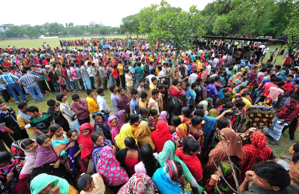 Garment workers employed at Rana Plaza, the garment factory building that collapsed, queue to receive wages from the Bangladesh Garment Manufacturers and Exporters Association in Savar, near Dhaka, Bangladesh, Tuesday, May 7, 2013. (AP)