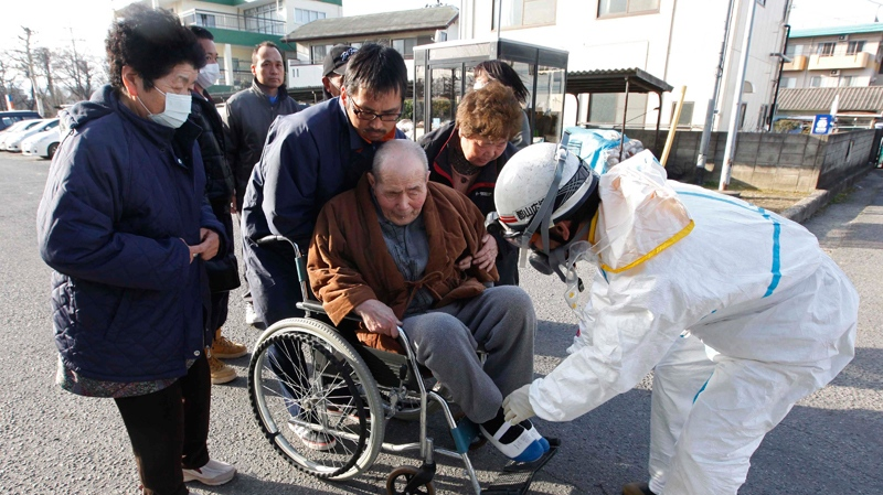 An elderly man is helped into a wheelchair to be scanned for levels of radiation in Koriyama, Fukushima Prefecture, Japan, Sunday, March 13, 2011. (AP / Mark Baker)