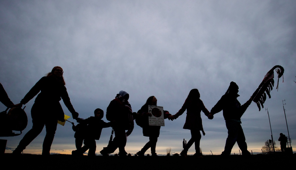 A group of First Nations protesters hold hands and dance in a circle during a demonstration in Surrey, B.C., in January 2013. (Darryl Dyck / THE CANADIAN PRESS)
