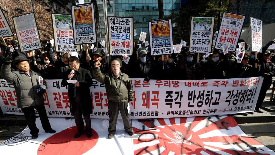 A South Korean protester wears a mask playing the role of Japan's Prime Minister Shinzo Abe and others shout slogans during a rally demanding full compensation and apology for wartime sex slaves from Japanese government and criticizing the Japanese government's recent claim over the disputed islets called Dokdo in South Korea and Takeshima in Japan, in front of the Japanese Embassy in Seoul, South Korea, Friday, March 1, 2013. (AP / Lee Jin-man)