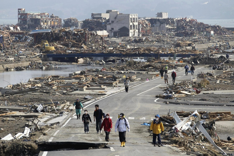 People walk a road between the rubble of destroyed buildings in Minamisanriku town, Miyagi Prefecture, northern Japan, Monday, March 14, 2011, three days after a powerful earthquake-triggered tsunami hit the country's east coast. (The Yomiuri Shimbun / Tsuyoshi Matsumoto)