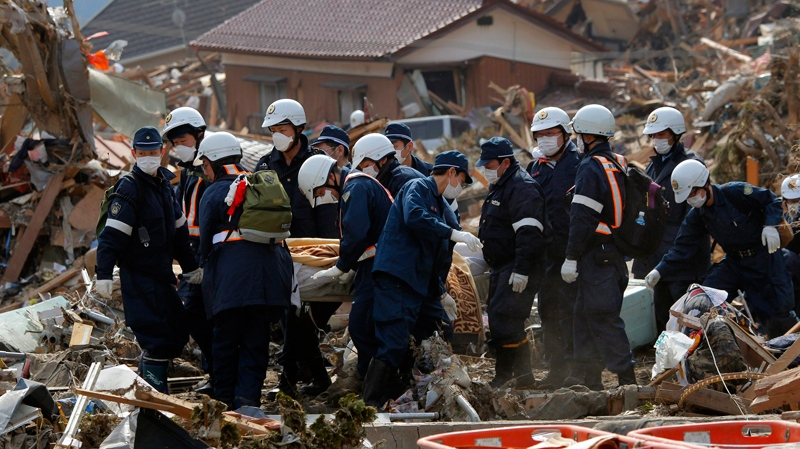 Police officers carry the body of a victim in Rikuzentakata, Iwate Prefecture, northern Japan, Monday, March 14, 2011, three days after northeastern coastal towns were devastated by an earthquake and tsunami. (AP / Itsuo Inouye)
