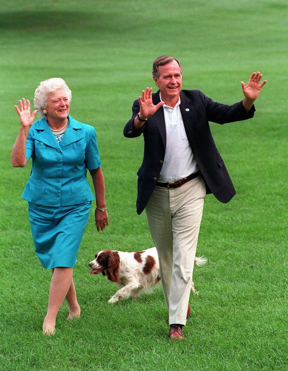 Former U.S. president Bush, right, and former U.S. first lady Barbara Bush walk with their dog, Millie, across the South Lawn as they return to the White House on Aug. 24, 1992. (AP / Scott Applewhite)