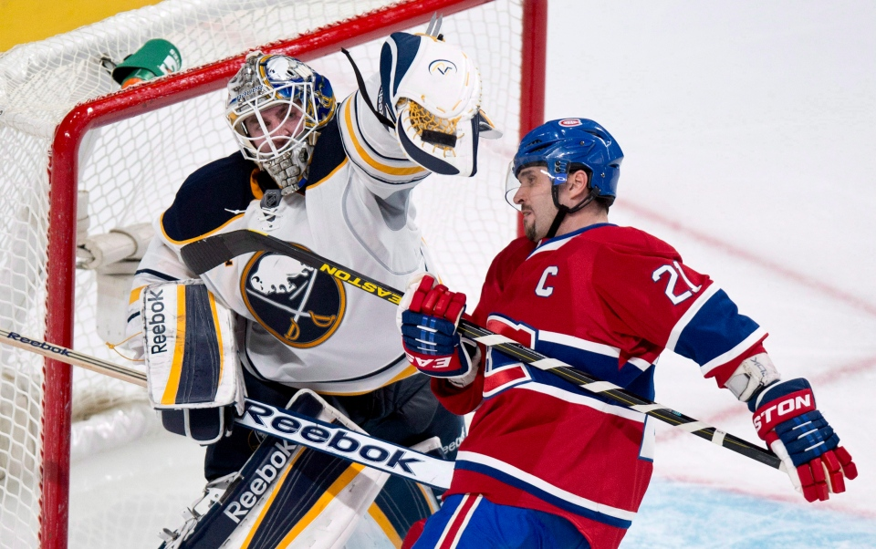Buffalo Sabres goalie Jhonas Enroth deflects a flying puck with his glove in front of Montreal Canadiens' Brian Gionta during third period NHL hockey action in Montreal on Tuesday, March 19, 2013. (The Canadian Press/Paul Chiasson)