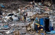 A firefighter sifts thorough the debris in Saito, Miyagi Prefecture, Monday, March 14, 2011 after Japan's biggest recorded earthquake slammed into its eastern coast Friday. (AP / Shuji Kajiyama)