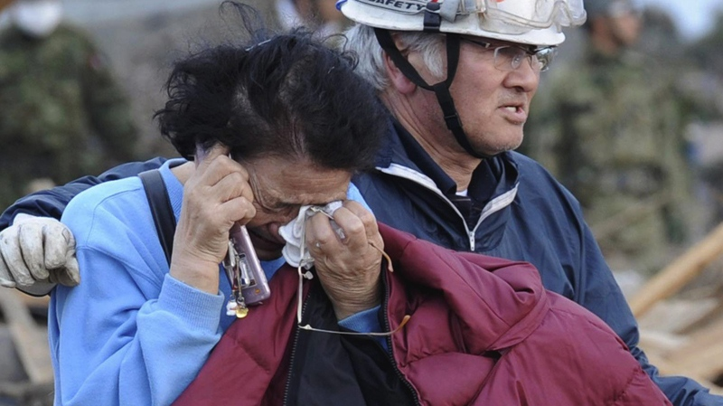 A man consoles a woman after she saw only the base of her house left in Noda village, northern Japan, Monday, March 14, 2011. (The Yomiuri Shimbun / Yoichi Hayashi)