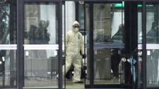 Officials wearing clothing to protect against radiation work in a centre to scan residents who have been within 20 kilometers of the Fukushima Dai-ichi nuclear plant damaged by Friday's earthquake Tuesday, March 15, 2011, in Koriyama, Fukushima Prefecture, Japan. (AP / Gregory Bull)