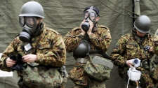 Japan Ground Self-Defense Force soldiers, mobilized to wash away radioactive material emitted from a nuclear power plant damaged by Friday's earthquake, put on protective gear on their arrival in Nihonmatsu, Fukushima Prefecture, Japan, Tuesday, March 15, 2011. (AP / Kyodo News)