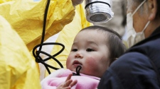 A baby is checked for radiation exposure level in Nihonmatsu in Fukushima prefecture on Tuesday, March 15, 2011. (AP / Kyodo News)