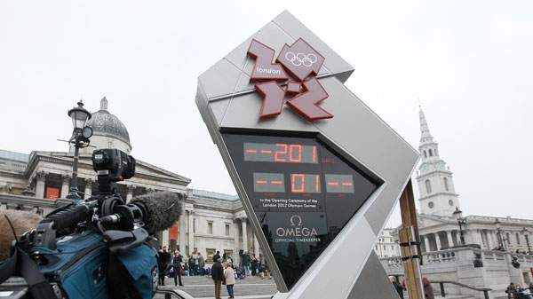 The official London 2012 Olympic countdown clock is attended to by technicians hours after it was started in Trafalgar Square in London, Tuesday March 15, 2011. (AP / Alastair Grant)