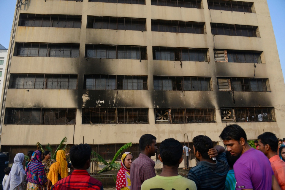 Workers stand outside an 11-storey building that houses the Tung Hai Sweater Ltd. factory and apartments after a fire in Dhaka, Bangladesh, Thursday, May 9, 2013. (AP Photo/Ismail Ferdous)