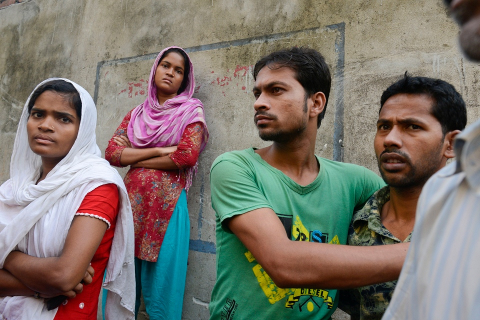 Workers stand outside an 11-story building that houses the Tung Hai Sweater Ltd. factory and apartments after a fire in Dhaka, Bangladesh, Thursday, May 9, 2013. (AP / Ismail Ferdous)