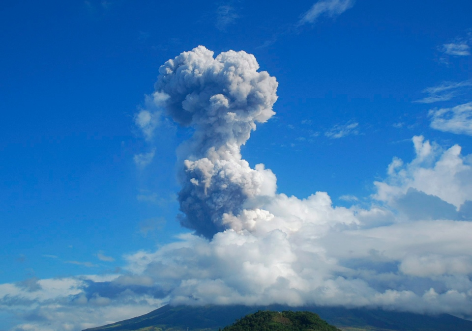 A cloud of volcanic ash shoots up to the sky as Mayon volcano, one of the Philippines' most active volcanoes, erupts after daybreak, viewed from Legazpi in Albay province in the central Philippines, Tuesday, May 7, 2013. (AP / Allan Imperial)