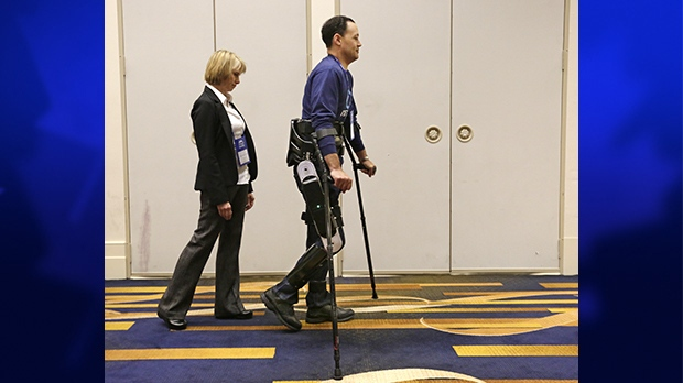 Michael Gore, centre, who is paralyzed from a spinal injury, walks with the use of the Indego wearable robot under the supervision of physical therapist Clare Hartigan during a meeting of the American Spinal Injury Association at a downtown hotel in Chicago, May 6, 2013. (AP / M. Spencer Green)