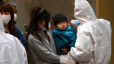 A child is screened for radiation exposure at a testing centre in Koriyama city, Fukushima Prefecture, Japan, Tuesday, March 15, 2011 after a nuclear power plant on the coast of the prefecture was damaged by Friday's earthquake. (AP / Wally Santana)