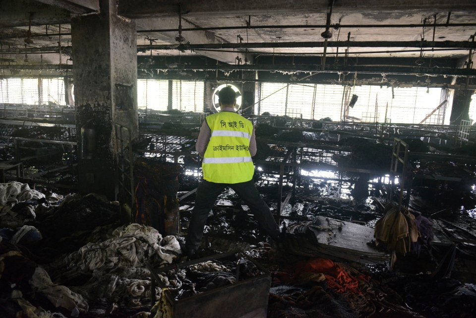 An investigator surveys the scene of a fire at a garment factory in Dhaka, Bangladesh, Thursday, May 9, 2013. (AP / Ismail Ferdous)