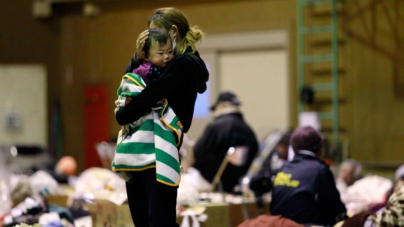 A woman holds her child at a shelter after being evacuated from areas around the Fukushima nuclear facilities damaged by last week's major earthquake and following tsunami, in Fukushima city, Fukushima prefecture, Japan, Wednesday, March 16, 2011. (AP / Wally Santana)