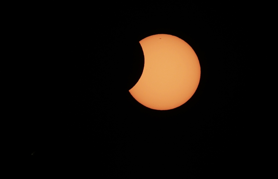 The moon begins to cross in front of the sun during a partial solar eclipse in Sydney, Friday, May 10, 2013. (AP / Rick Rycroft)