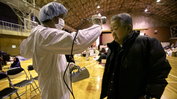 A man is screened for radiation exposure at a shelter after being evacuated from areas around the Fukushima nuclear facilities damaged by last week's major earthquake and following tsunami, Wednesday, March 16, 2011, in Fukushima city, Fukushima prefecture, Japan. (AP / Wally Santana)