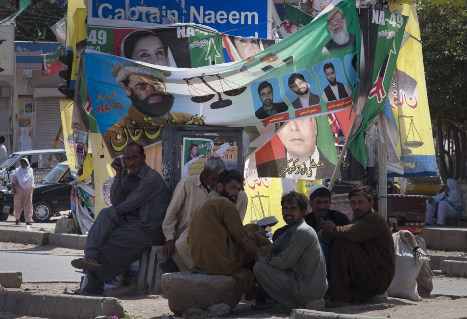 Pakistani labourers wait for people to hire them on daily wages, sit under banners of candidates take part in elections on Friday, May 10, 2013 at a roadside in Islamabad, Pakistan. (AP / B.K. Bangash)