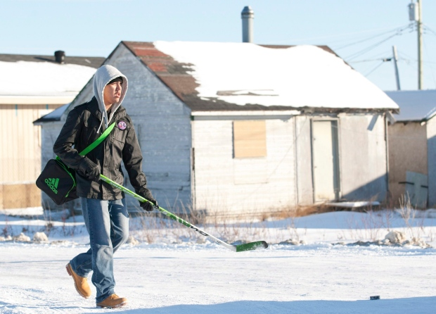 A youth walks past a boarded-up house in Attawapiskat, Ont., on Tuesday, Nov. 29, 2011. (The Canadian Press/Adrian Wyld)
