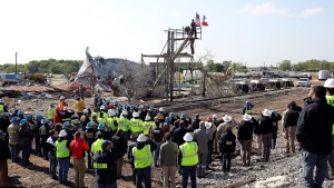 Workers pause for a memorial service at the site of the fire and explosion in West, Texas on Wednesday, April 24, 2013. (The San Antonio Express-News, Tom Reel, Pool)