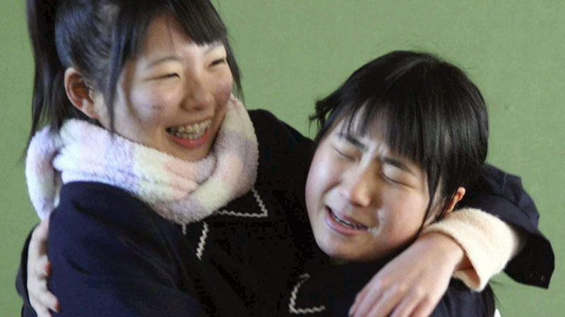 Students embrace each other as they were reunited at the graduation of an junior high school in Miyako, northern Japan Thursday, March 17, 2011 following Friday's massive earthquake and tsunami. (AP / Yomiuri Shimbun, Takashi Ozaki)