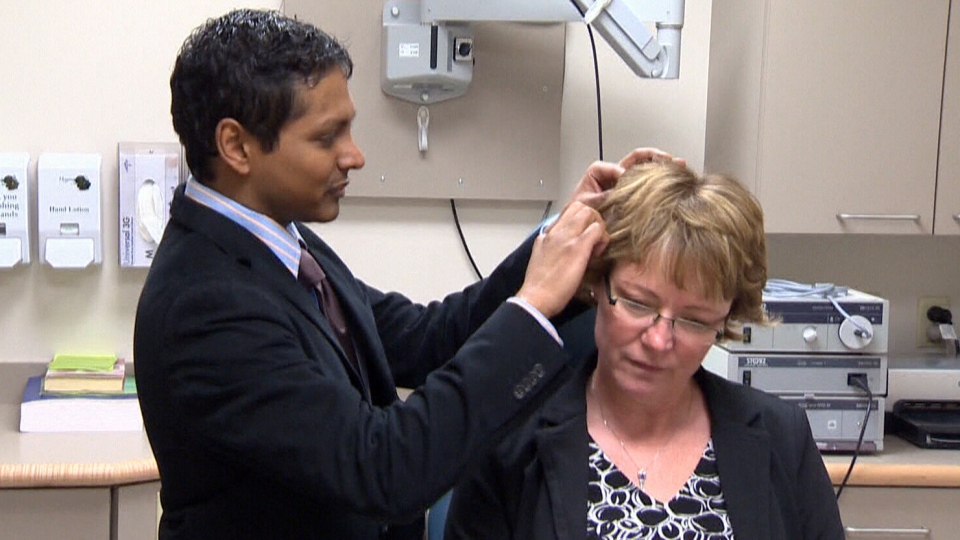 Dr. Sumit Agrawal checks a hearing aid implanted in the scalp of Kelly Dickson in his London, Ont. office.