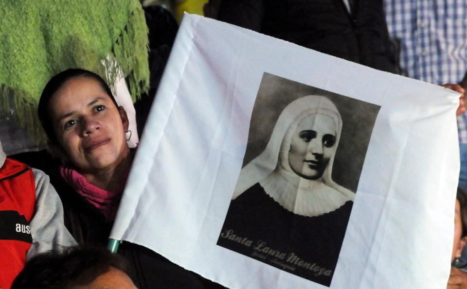 A woman holding a poster of Mother Laura Montoya watches her beatification ceremony on a giant TV screen in her hometown of Jerico, Colombia, Sunday, May 12, 2013. (AP / Luis Benavides)