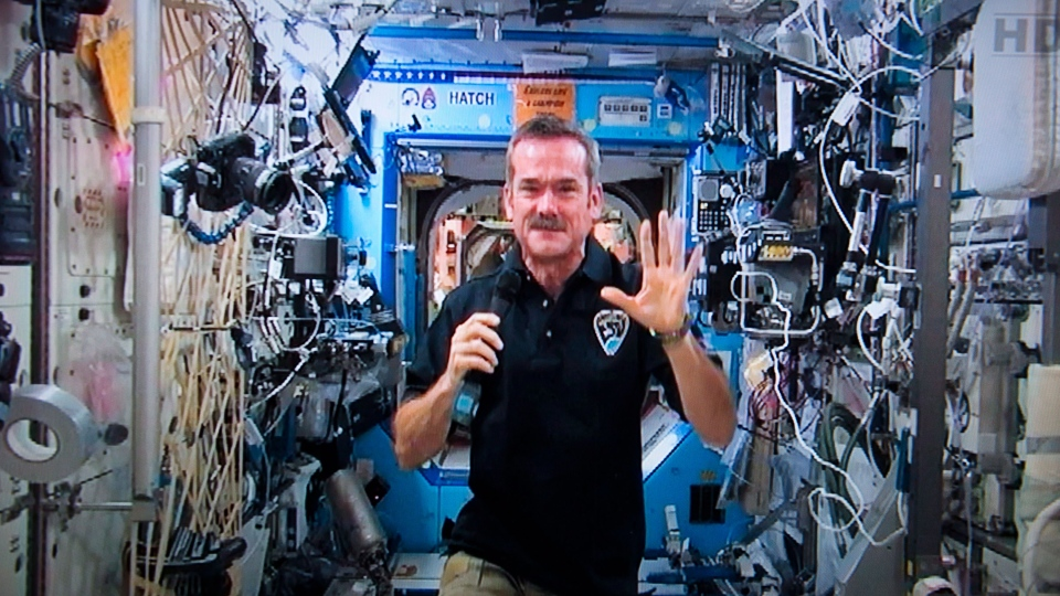 Canadian astronaut Chris Hadfield waves goodbye at the end of a news conference from the International Space Station on a photograph taken from a television monitor in St-Hubert, Que. Thursday, Jan. 10, 2013. (Paul Chiasson / THE CANADIAN PRESS)