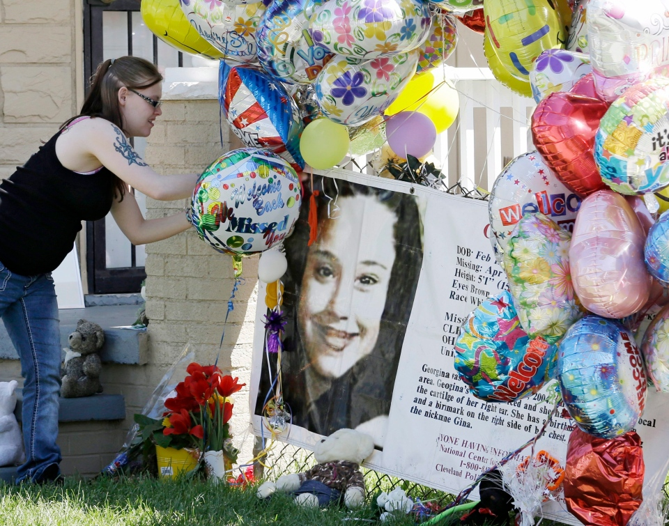 A girl adds a balloon outside the home of Gina DeJesus Thursday, May 9, 2013, in Cleveland. (AP / Tony Dejak)