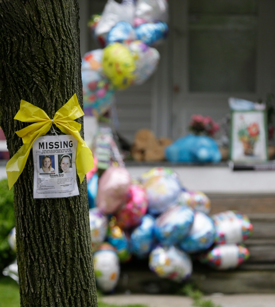 A missing poster still hangs on a tree at the home where Amanda Berry is staying in Cleveland on Saturday, May 11, 2013. (AP / Tony Dejak)