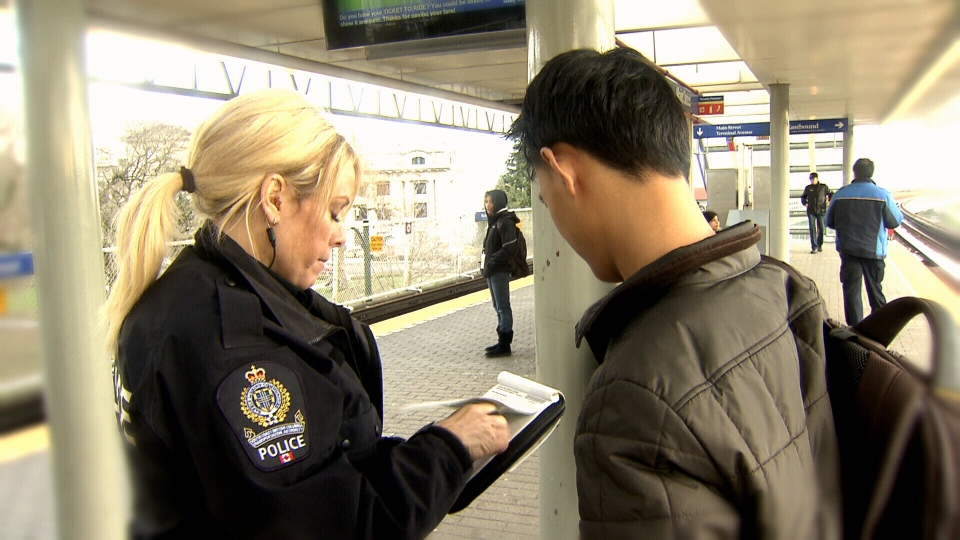 A TransLink police officer gives out a ticket at a SkyTrain station.