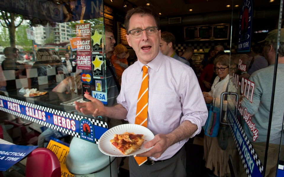 B.C. NDP Leader Adrian Dix carries a slice of pizza as he leaves after a campaign stop at Nat's New York Pizza in Vancouver, B.C., on Saturday May 11, 2013. (Darryl Dyck / THE CANADIAN PRESS)
