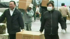 Rescuers and victims carry out bags of food aid from a ship in northern Japan Thursday, March 17, 2011.