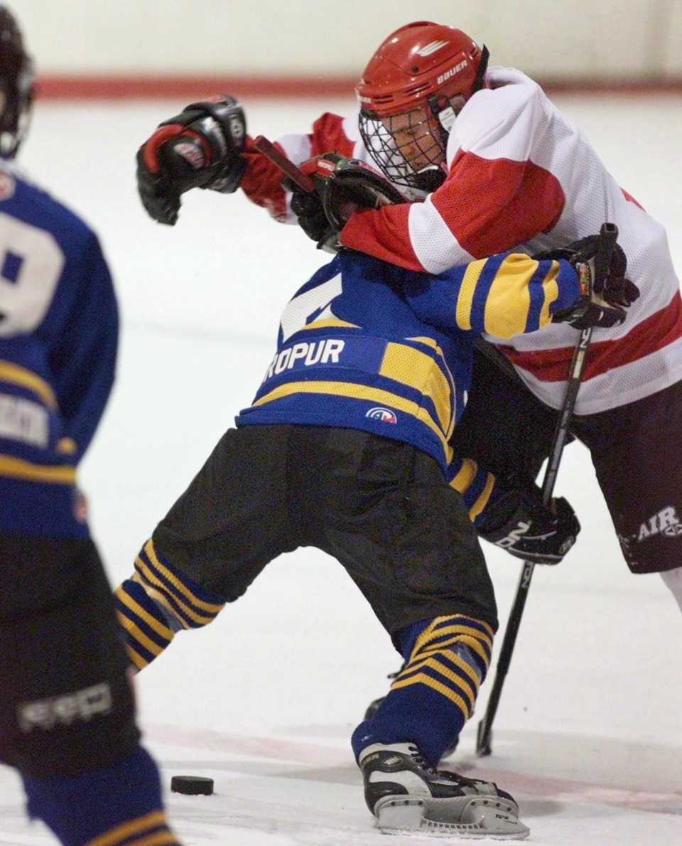 A player from the Dartmouth Whalers collides with a member of the Cole Harbour Red Wings, right, in peewee 'A' action in Halifax on Thursday Feb. 15, 2001. (Andrew Vaughan / THE CANADIAN PRESS)