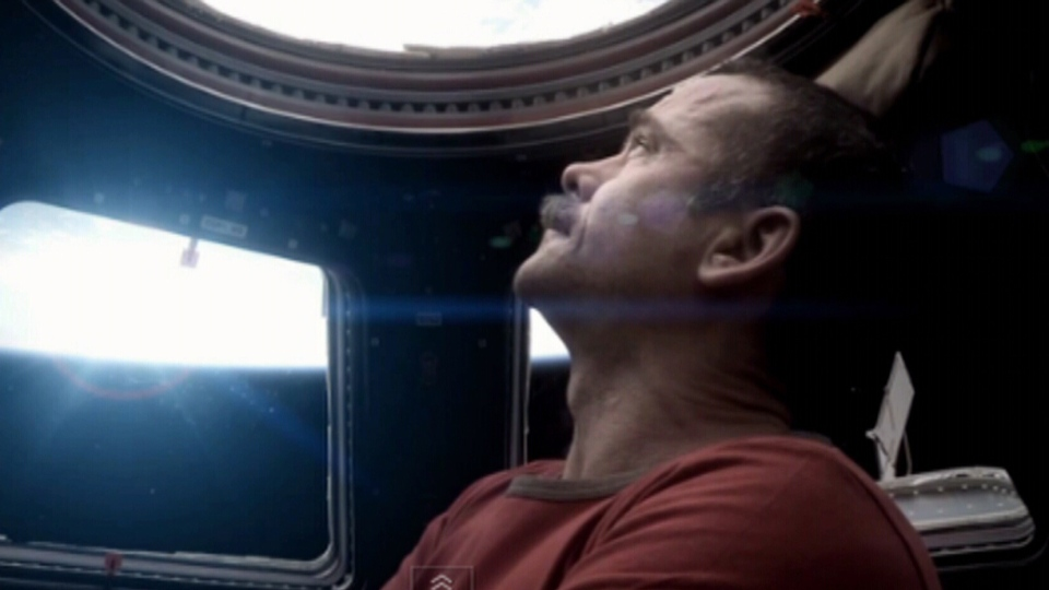 Canadian astronaut Chris Hadfield looks out of the observatory module of the International Space Station, in this image taken from the first music video shot in space, Chris Hadfield's cover version of David Bowie's Space Oddity.