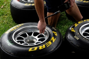 A mechanic checks the pressures in a new set of Pirelli tires ahead of the Australian Grand Prix in Melbourne, Australia, Thursday, March 24, 2011. (AP Photo/Rob Griffith)