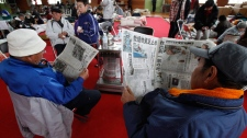 Men read newspapers at a makeshift shelter in Ofunato, Iwate Prefecture, northern Japan, Thursday, March 17, 2011.(AP / Shizuo Kambayashi)