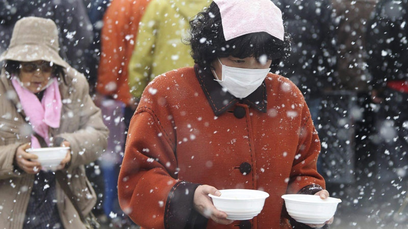 Evacuees carry bowls of pork soup from a soup kitchen back to their makeshift shelter in Minamisanriku, northern Japan, Wednesday, March 16, 2011, after Friday's earthquake and tsunami. (The Yomiuri Shimbun / Tsuyoshi Matsumoto)