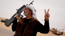 A Libyan rebel poses near a tank captured from Libyan government forces, on the frontline near Sultan, south of Benghazi, Libya, Friday, March 18, 2011. (AP Photo/Anja Niedringhaus)