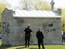 Quebec Provincial Police investigators look at graffiti left overnight on the tomb of former prime minister Pierre Trudeau, in St. Remi, Quebec, Saturday April 26, 2008. (Peter McCabe / THE CANADIAN PRESS)