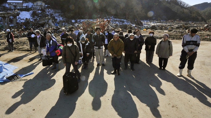 Quake survivors observe a moment of silence at the time the massive earthquake struck their village of Tanohata, northeastern Japan, Friday, March 18, 2011. (Kyodo News)