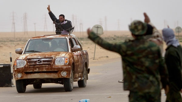 Libyan rebels flash the victory sign as they ride on top of a car with heavy weapons on the frontline near Sultan, south of Benghazi, Libya, Friday, March 18, 2011. (AP / Anja Niedringhaus)