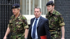 British Defence Secretary Liam Fox, centre, with British Chief of Defence Staff General Sir David Richards arrive in Downing Street for meeting about the UN resolution on the 'No Fly Zone in Libya', in London, Friday, March, 18, 2011. (AP / Anthony Devlin)